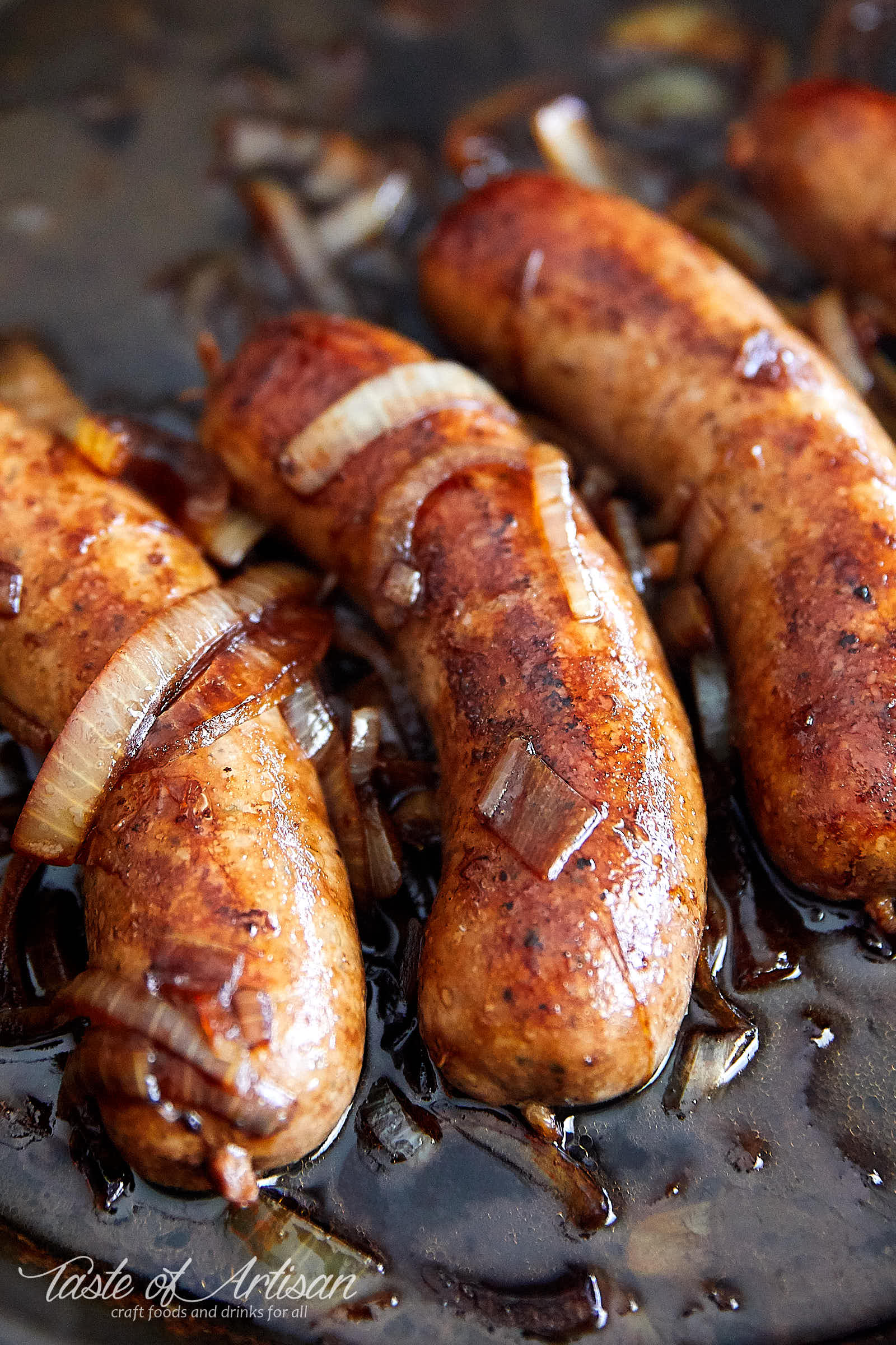 Homemade German Bratwurst frying in a pan.