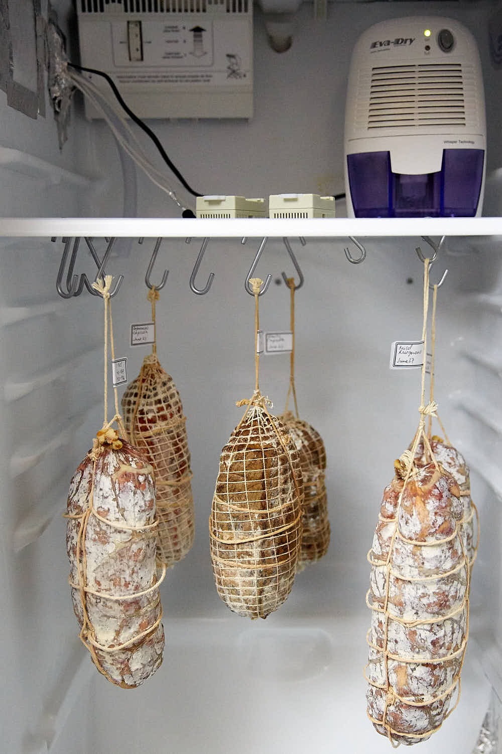 Meats hanging inside a curing chamber.