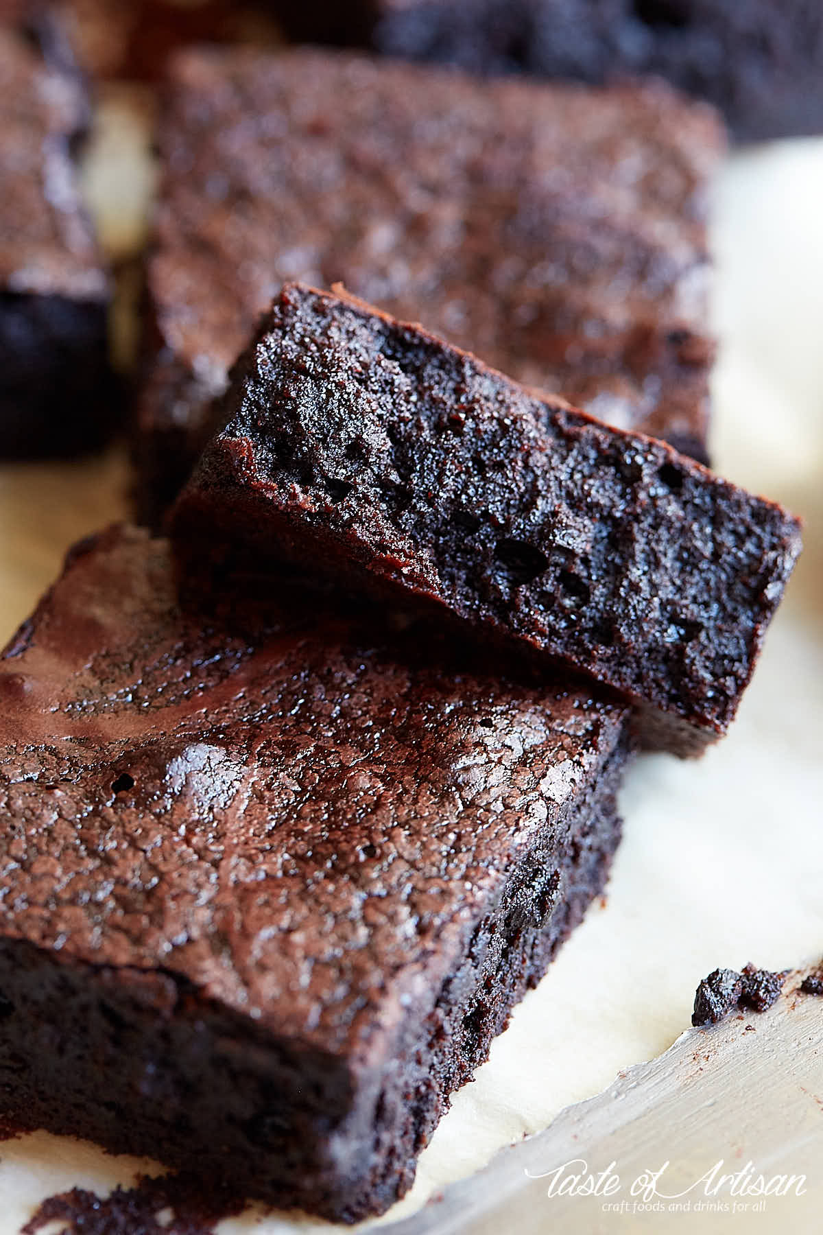 Flourless brownies, cut into pieces, set on a piece of paper.