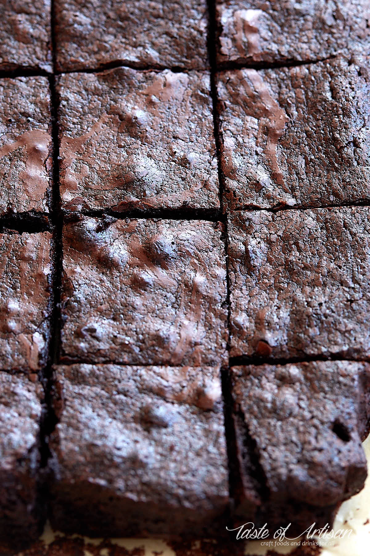Flourless brownie, cut into squares, inside a baking dish.