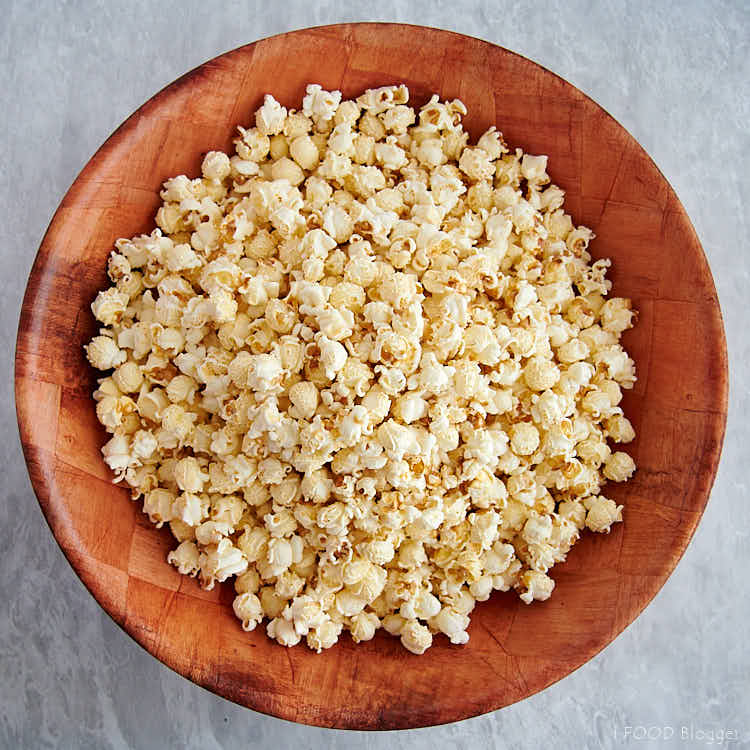 A large bamboo bowl filled with popped popcorn.