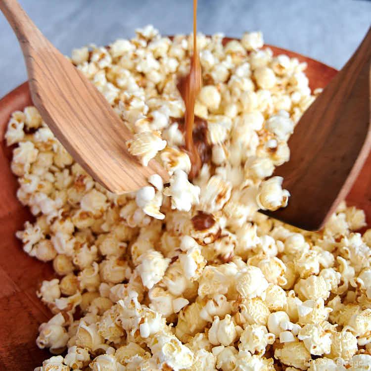 Mixing popcorn and caramel sauce to make caramel popcorn.