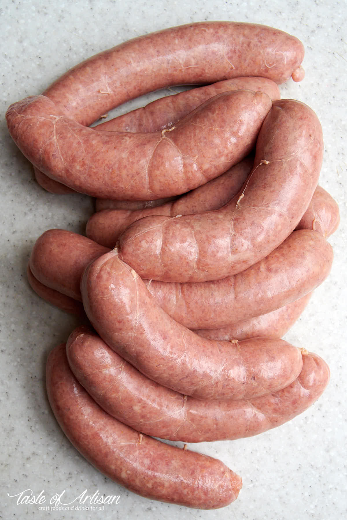 Raw Bockwurst sausage links on a grey table surface.