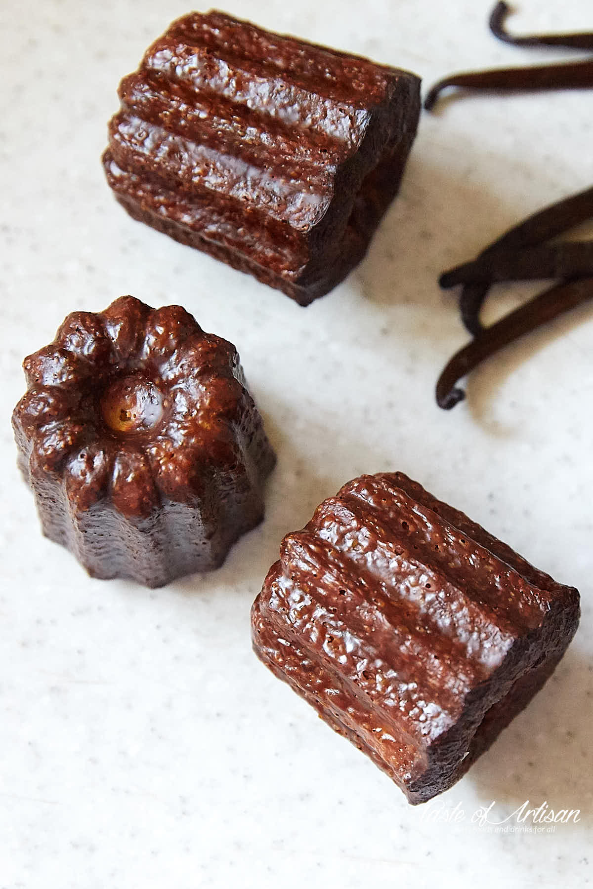 Caneles and vanilla beans on a white table top.