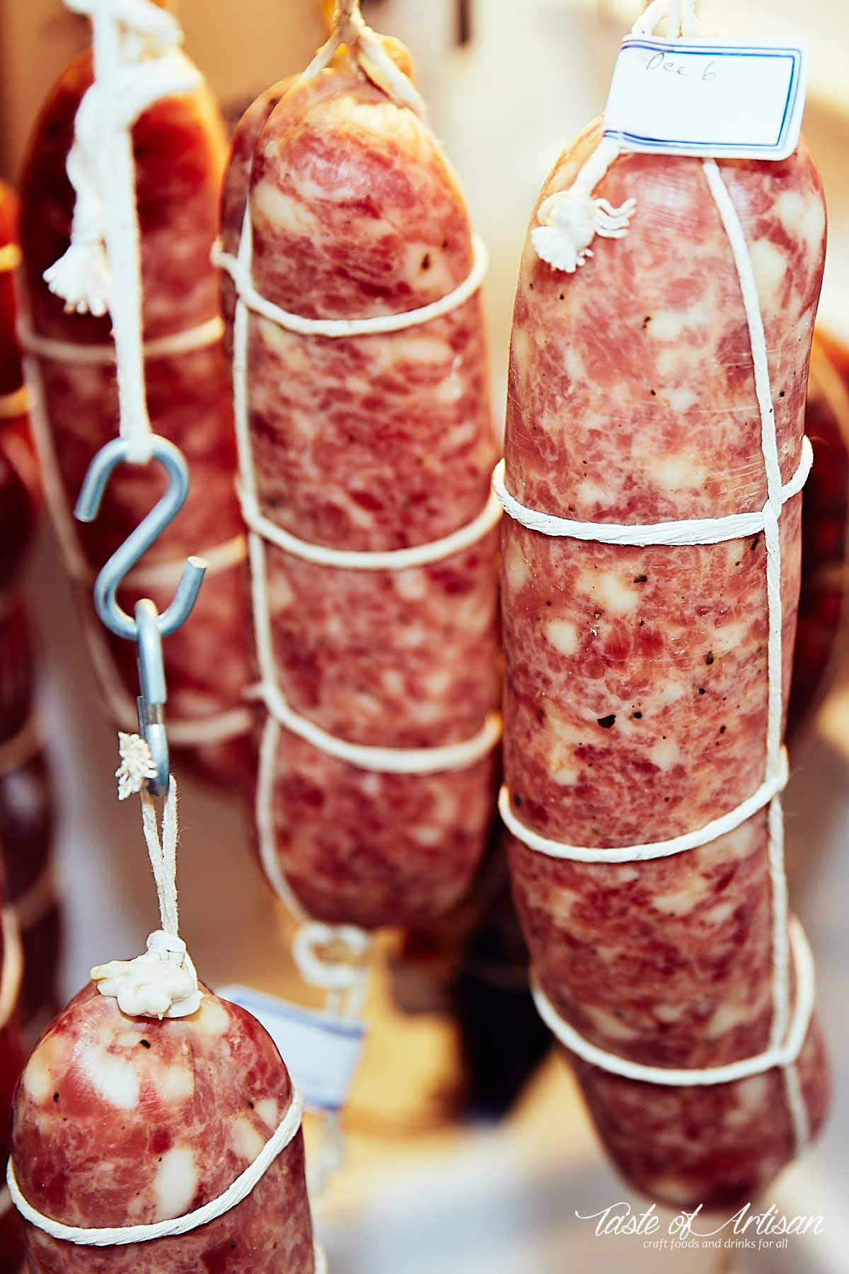 Soppressata, tied with twine, hanging in a meat curing fridge.
