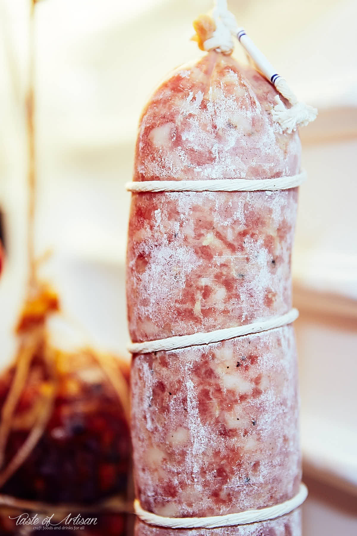 Sopressata (soppressata), covered in white mold, inside a curing chamber..