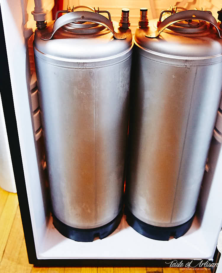 Two kegs inside a bar fridge with carbonated water.