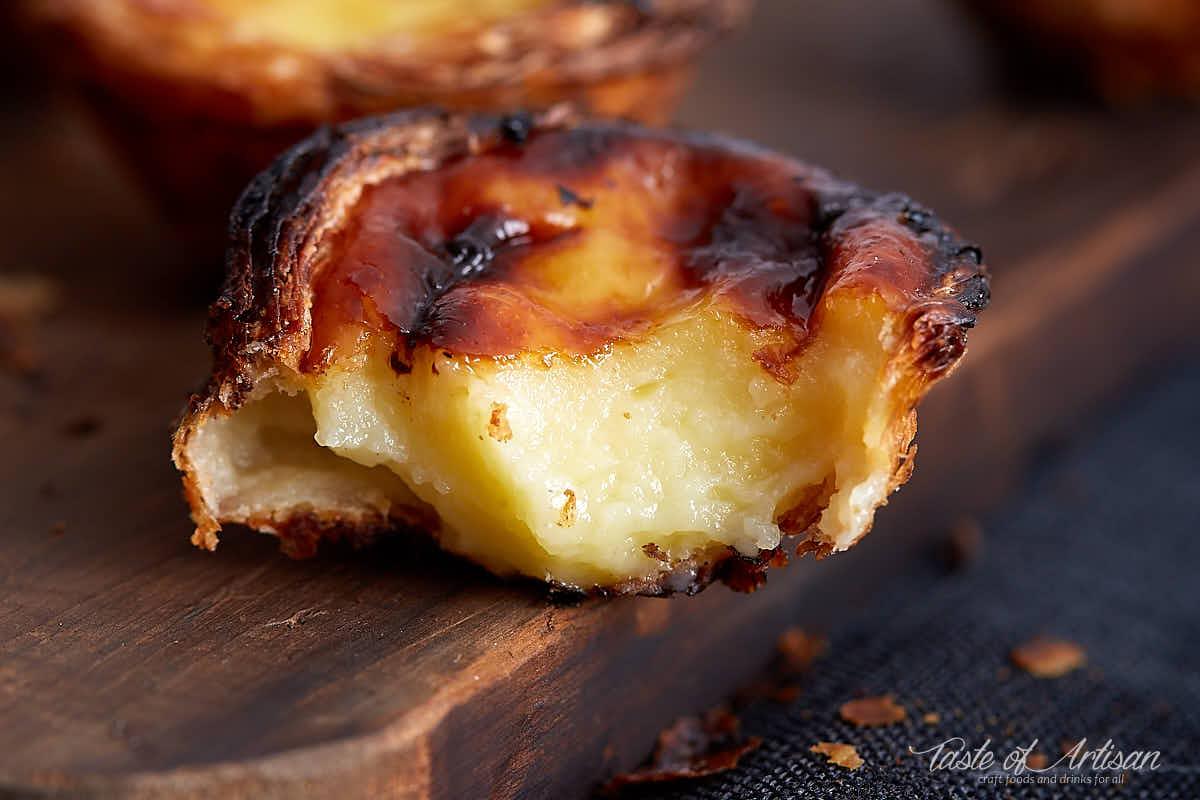 Portuguese custard tart, a piece bitten off, close up of moist custard, on a cutting board.