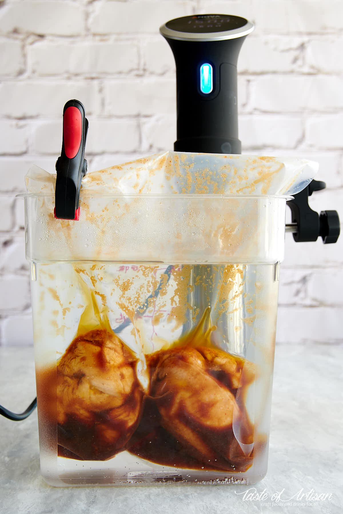 Two chicken breasts in a vacuum sealed bag with sauce cooking inside a clear container filled with water and with a sous vide circulator.