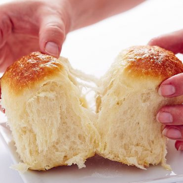 Two hands pulling two yeast rolls apart, flaky dough visible.