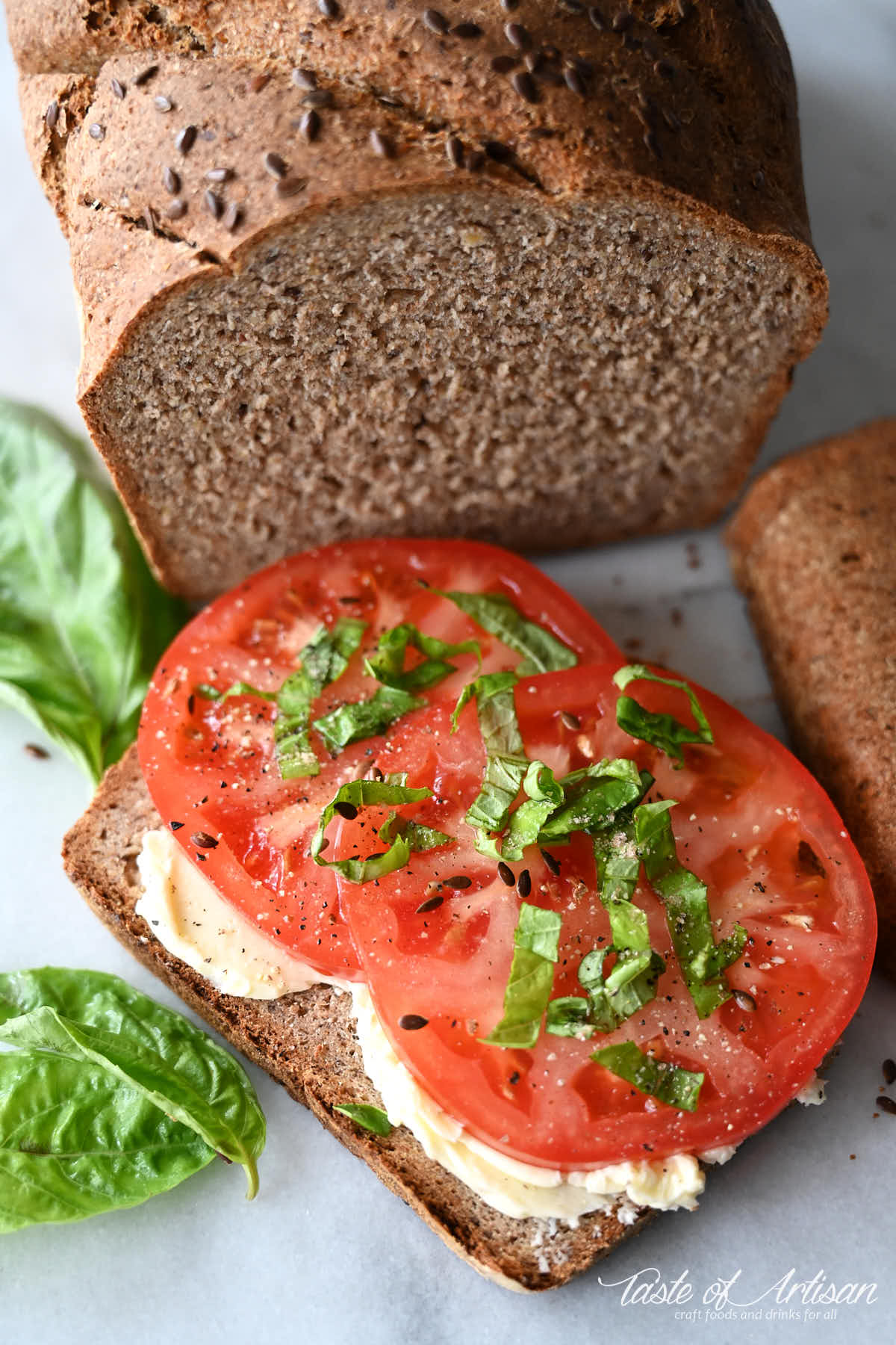 A slice of flaxseed bread with butter and slices of tomatoes and chopped basil on top.