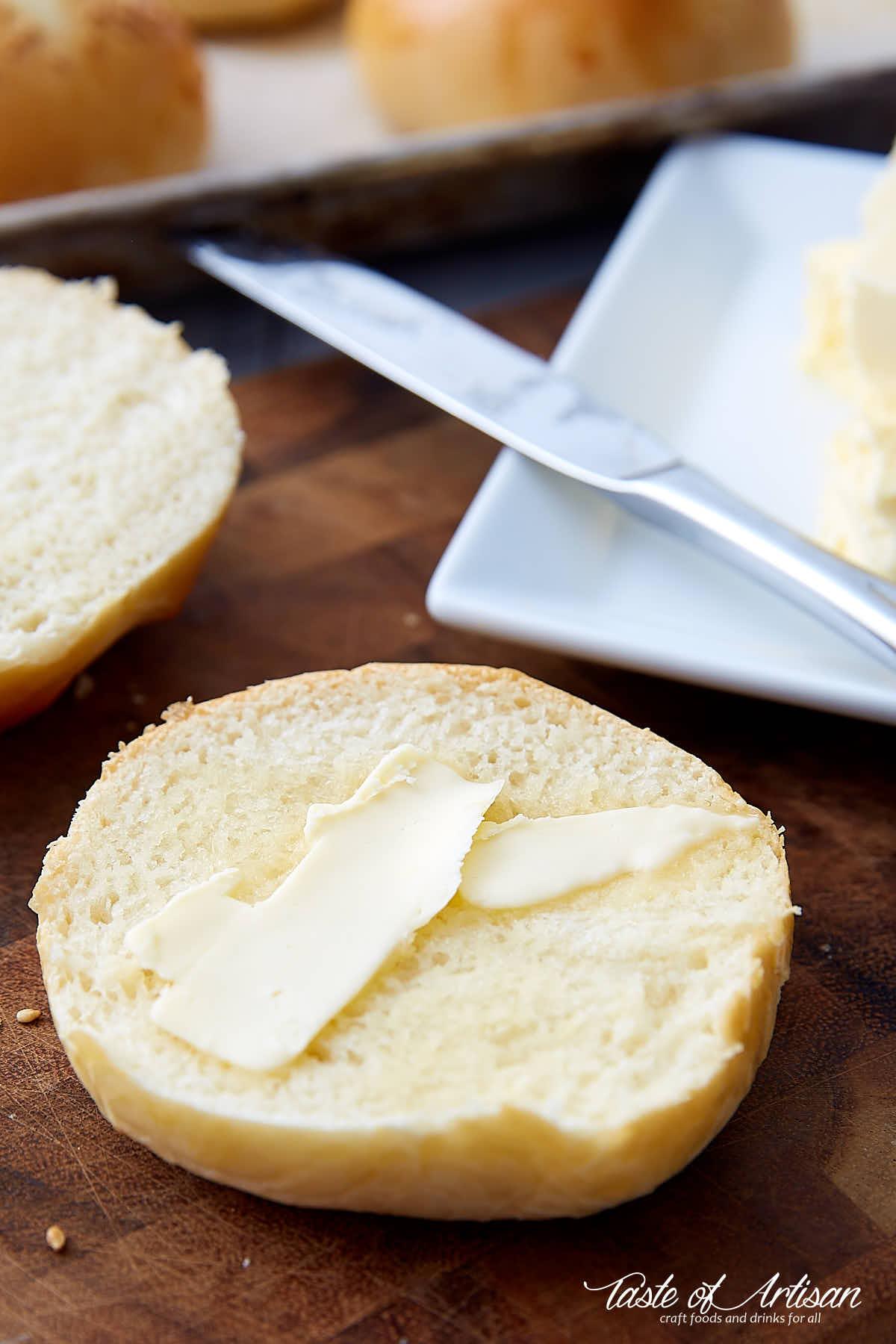A cut in half brioche bun with butter spread on top.