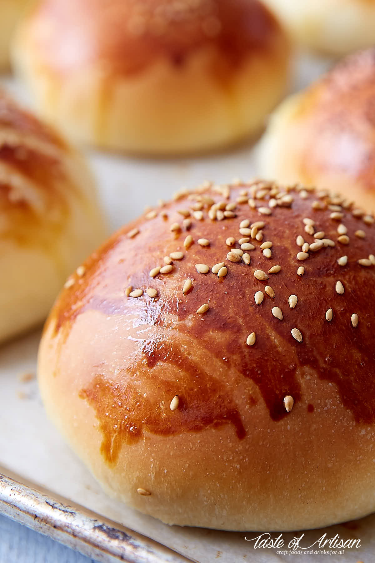 A close up of golden brown brioche bun with sesame seeds on top.