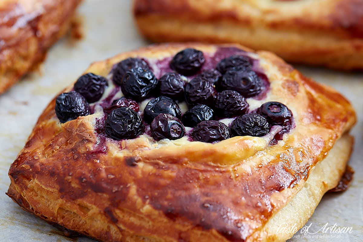 Close up of a cheese danish topped with blueberries.