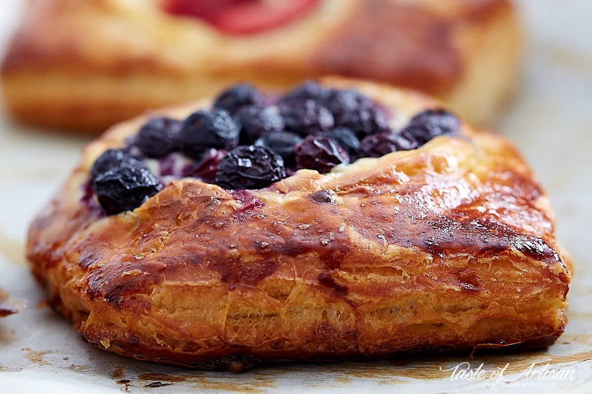 Side view of a cheese danish topped with blueberries.