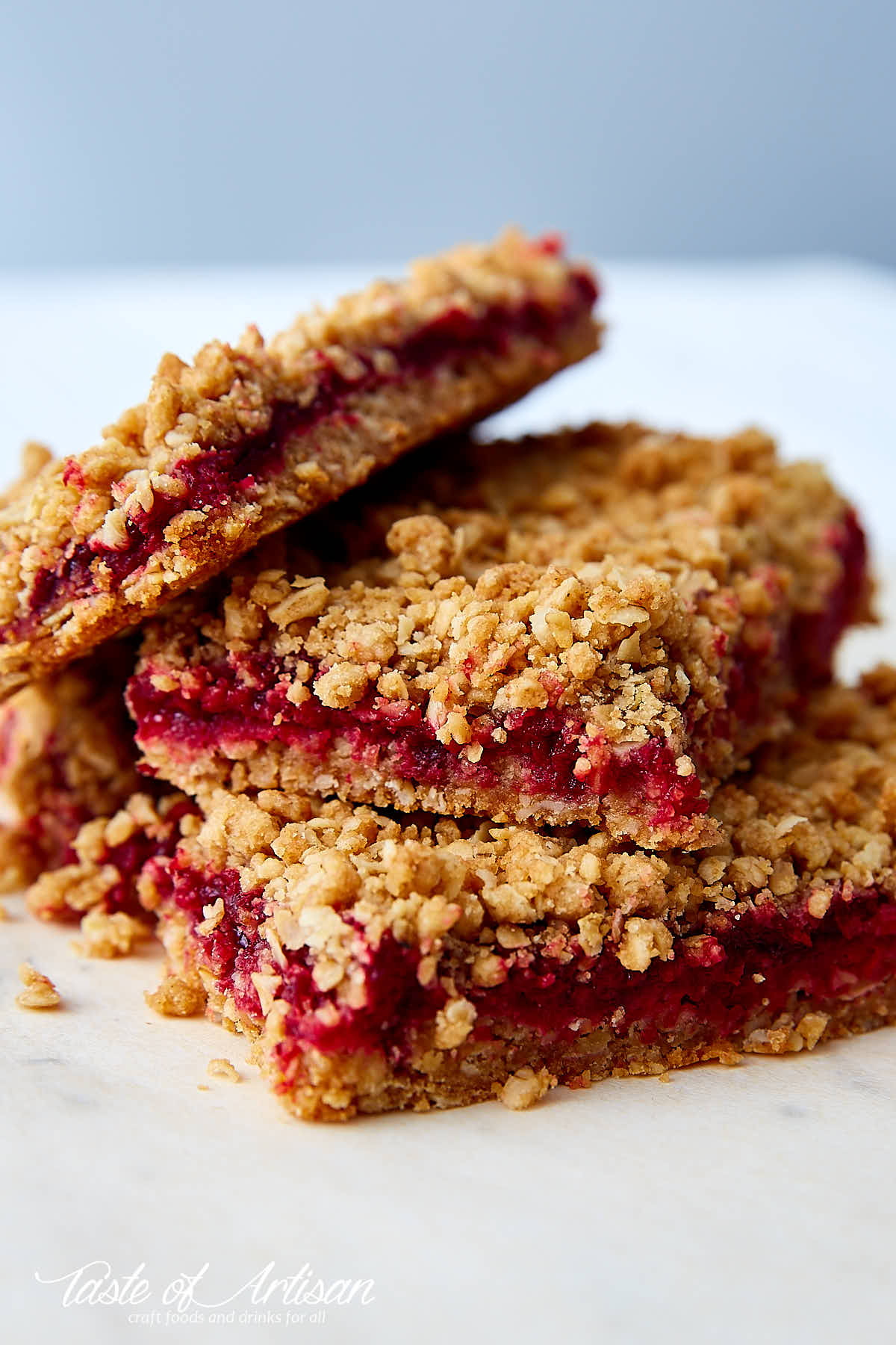 Cherry oat bars stacked on top each other on a table.