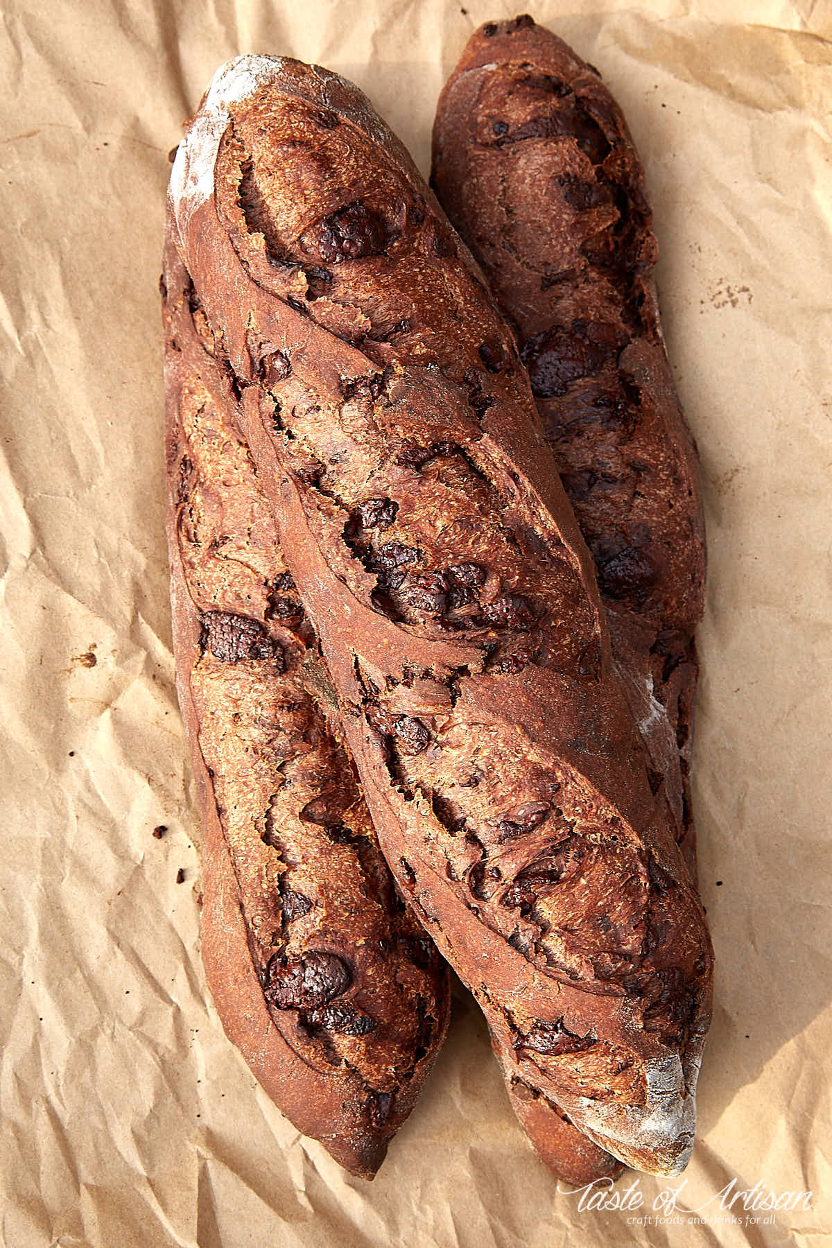 Three chocolate baguettes on a piece of brown paper.