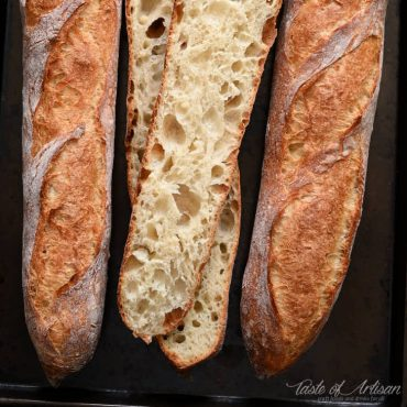 Three homemade French baguettes on a baking sheet, one cut open in half showing airy crumb.
