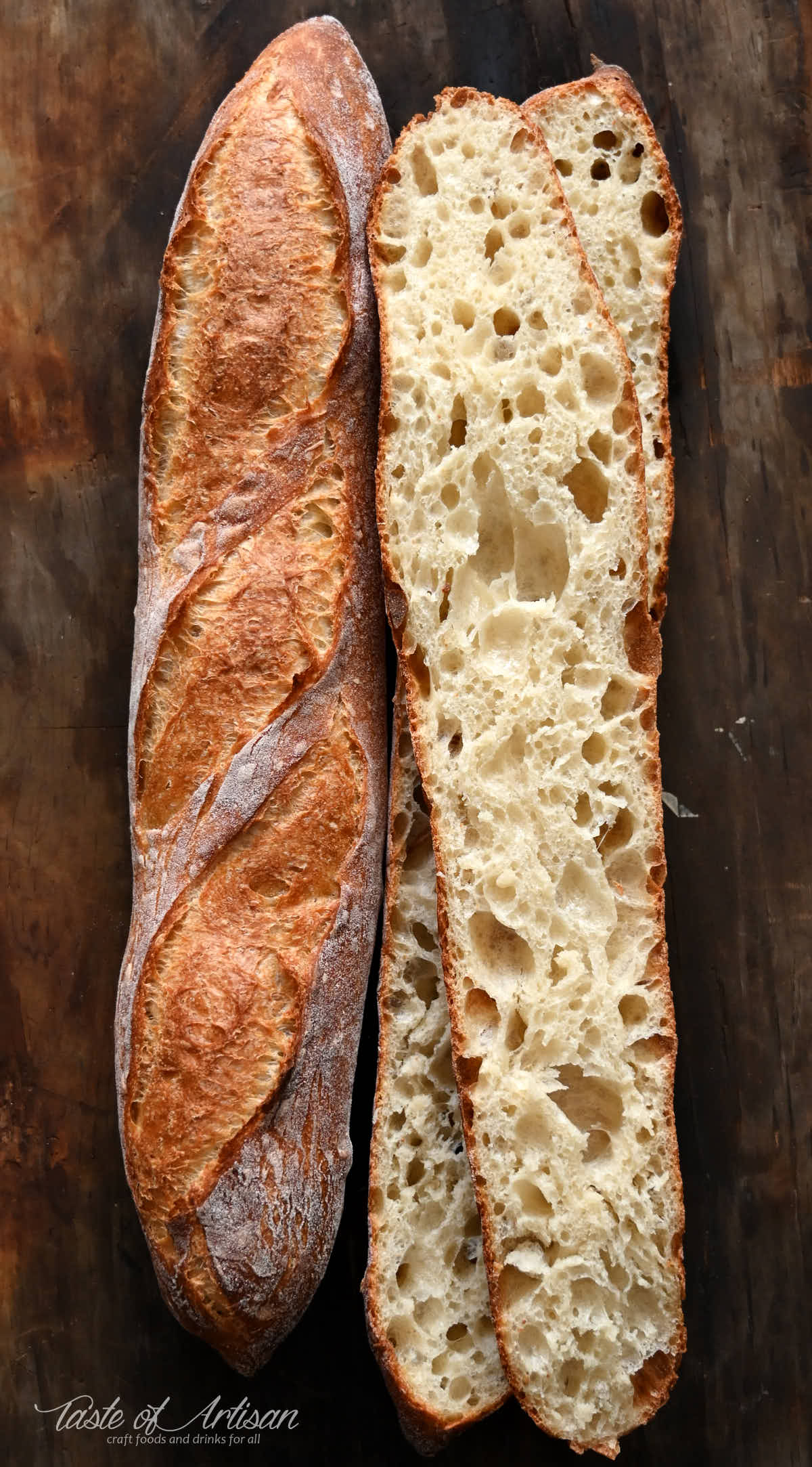 Two homemade French baguettes on a baking sheet, one cut open in half showing airy crumb.