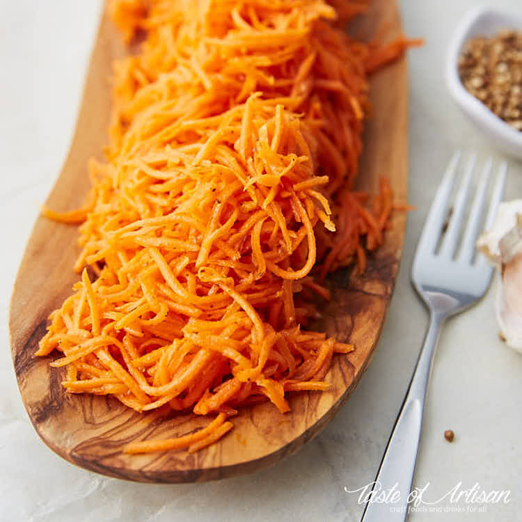 Marinated carrots on a wooden serving platter.