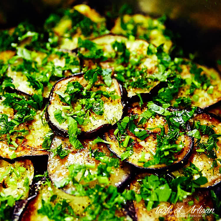 Close up of marinated eggplant slices sprinkled with chopped greens.