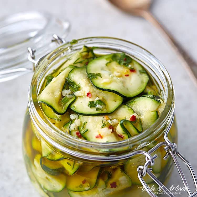 Sliced marinated zucchini in a glass jar.