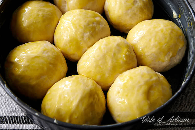 Pampushki dough balls brushed with egg yolk.