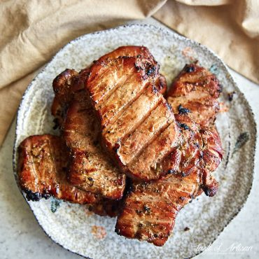 Smoked pork chops, deep brown, on a platter.