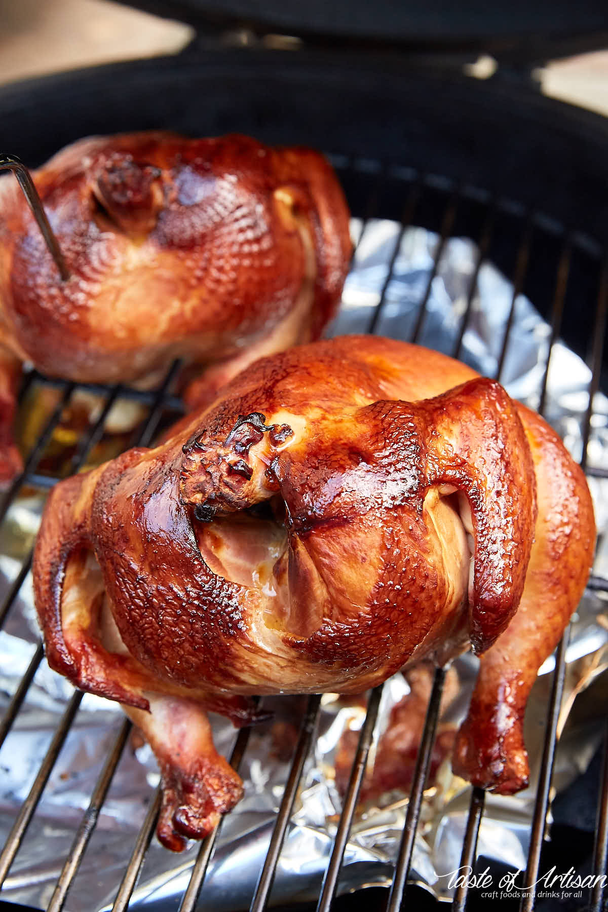 Two golden brown chickens on a smoker rack.