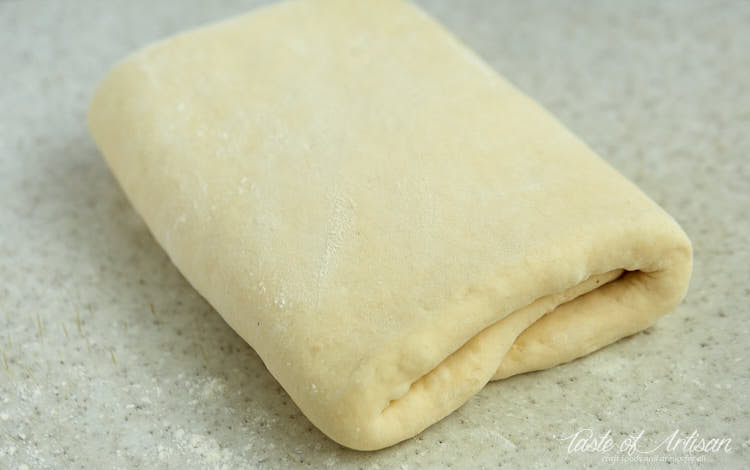 Dough folded with butter inside. Croissant dough lamination.