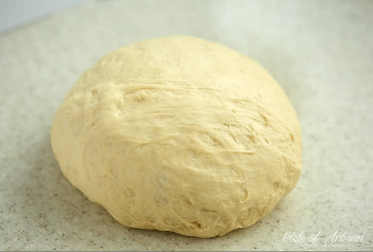 A ball of dough for croissants on a table.