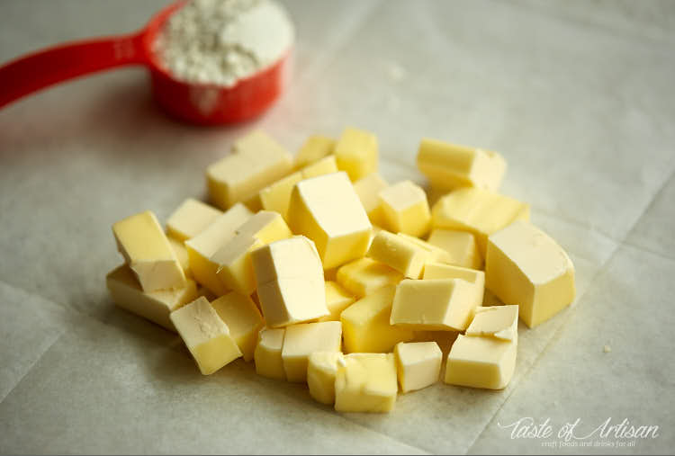 Cubed butter on a piece of parchment paper.