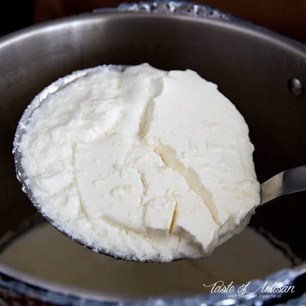 Ladling curd from the pot into a draining bowl.