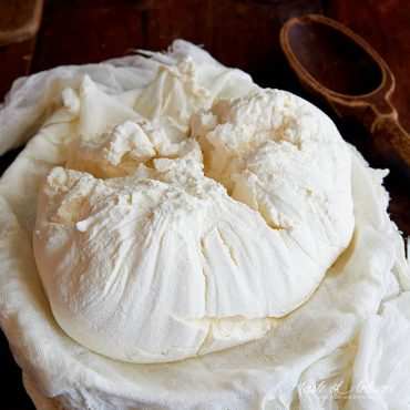 A bowl lined with muslin full of freshly made cream cheese.