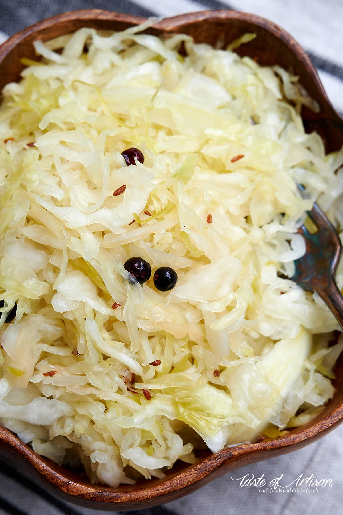 Top down view of a brown wooden bowl with homemade sauerkraut and a fork.