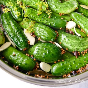 Close up of whole pickles in pickling juice in a pot.