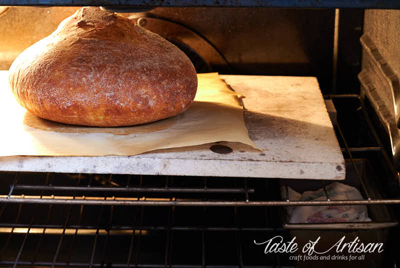 Bread baking in oven on pizza stone.