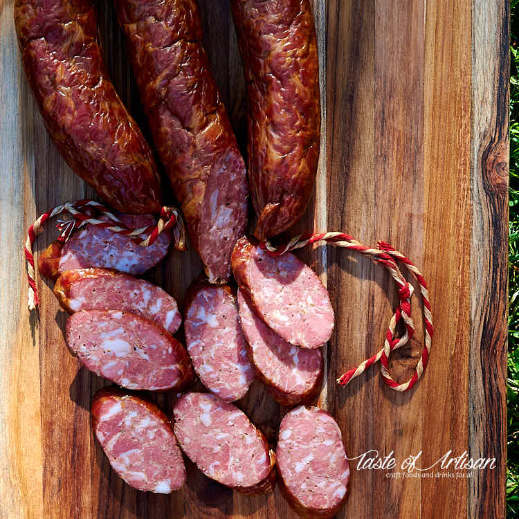 Sliced Andouille Sausage on a brown cutting board.