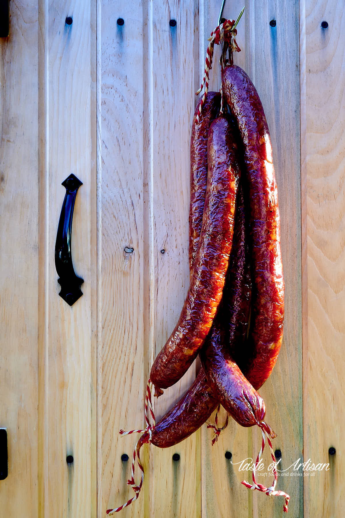 Smoked Andouille sausages hanging on the door or a smokehouse. Rich mahogany color.