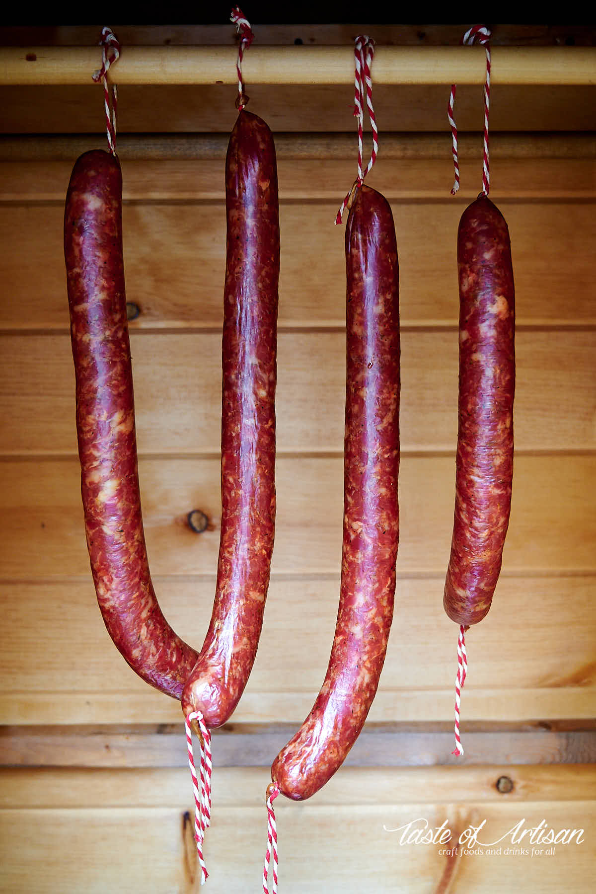 Andouille sausages hanging on a stick and smoking inside a smokehouse.
