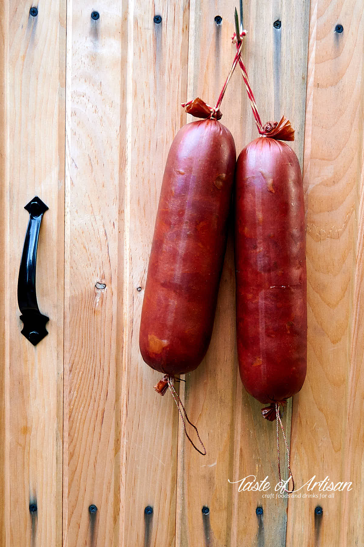 Krakow sausage hanging from the door of a smokehouse.