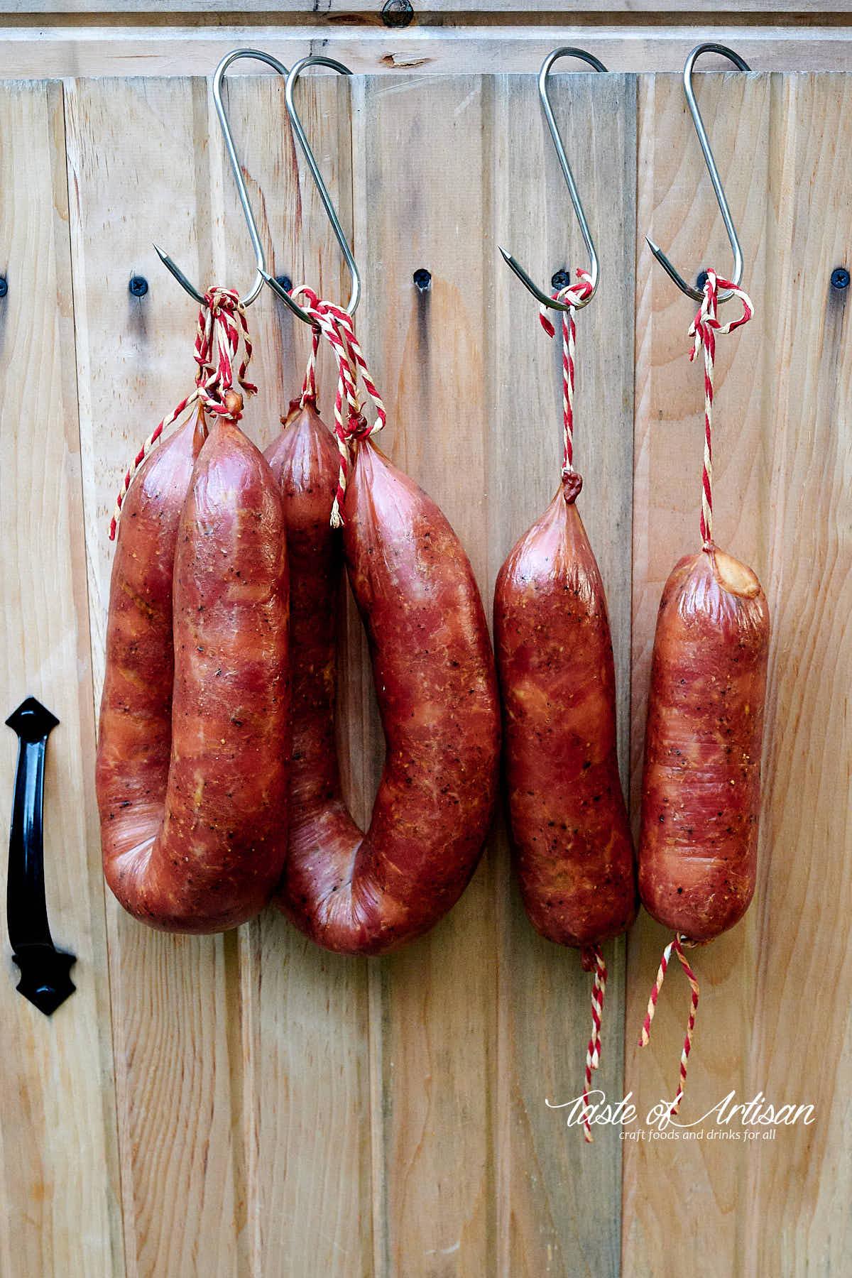 Smoked kielbasa rings hanging on the door of a smokehouse.