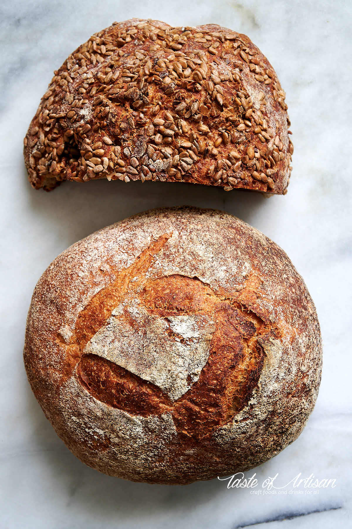 Whole what and rye no knead bread loaves on a marble table.
