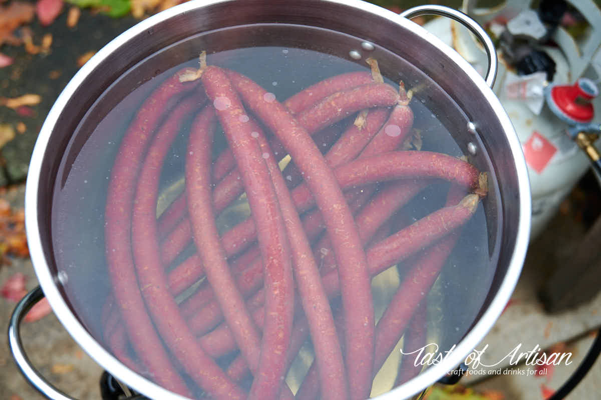 Smoked beef sticks poaching in hot water.