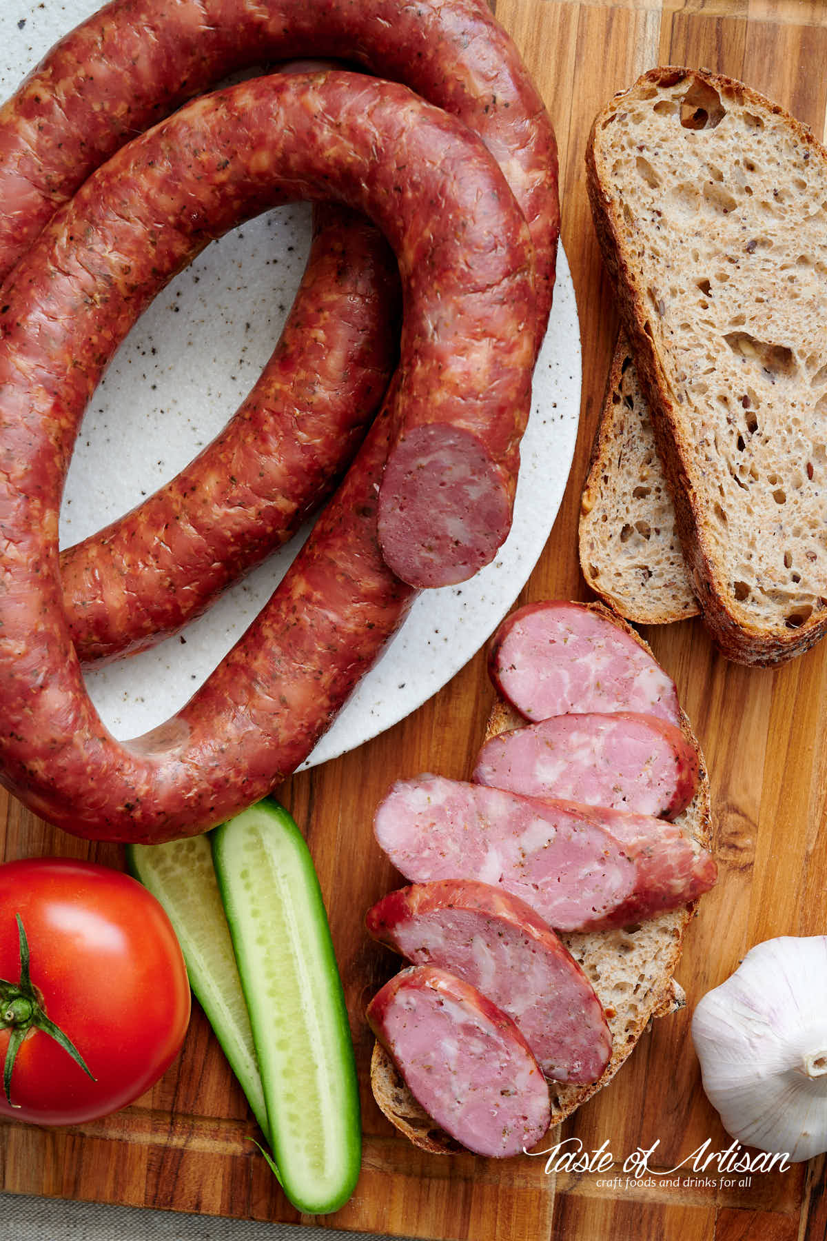 Whole and pieces of sliced garlic sausage on a table, with sliced bread and vegetables.