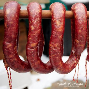 Smoked garlic sausage hanging on a stick.
