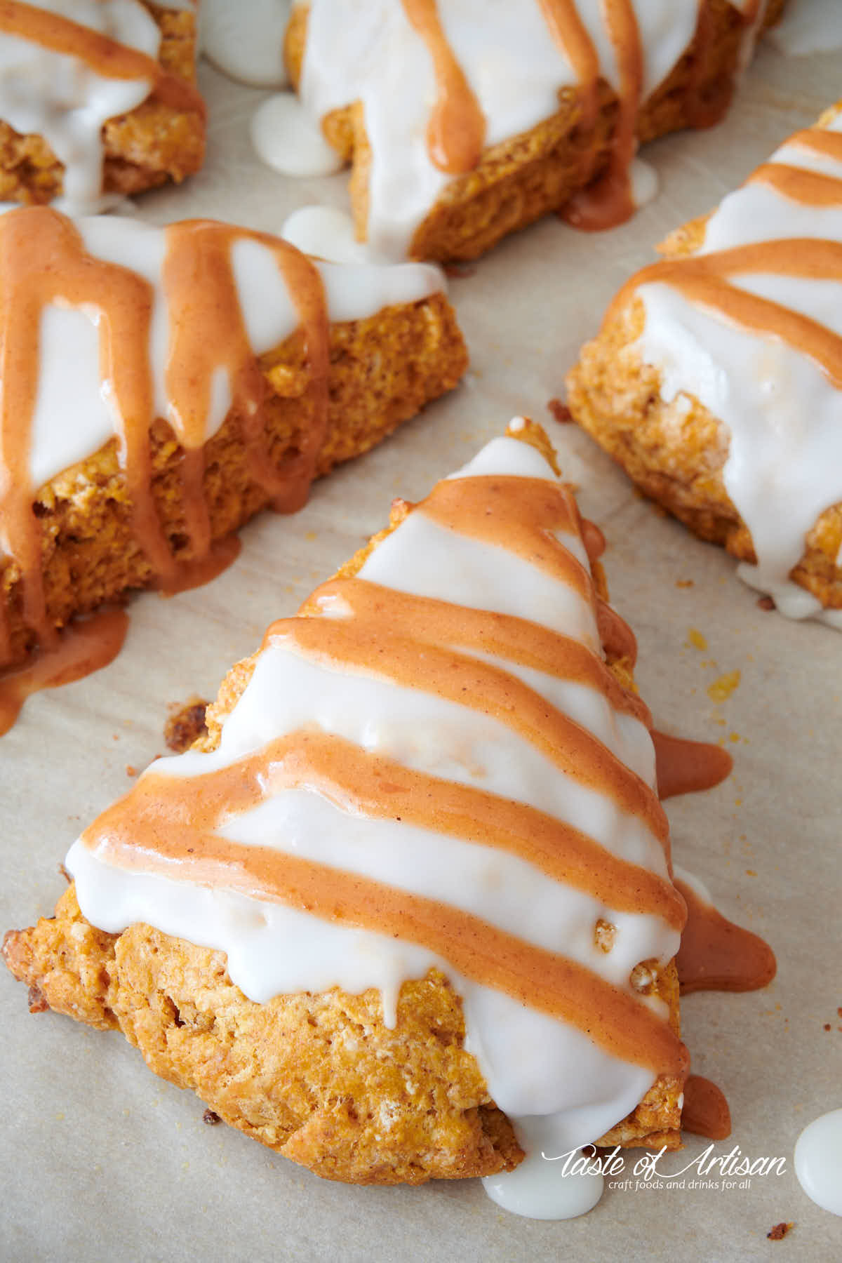 Pumpkin scones, covered with white glaze and stripes of orange glaze.