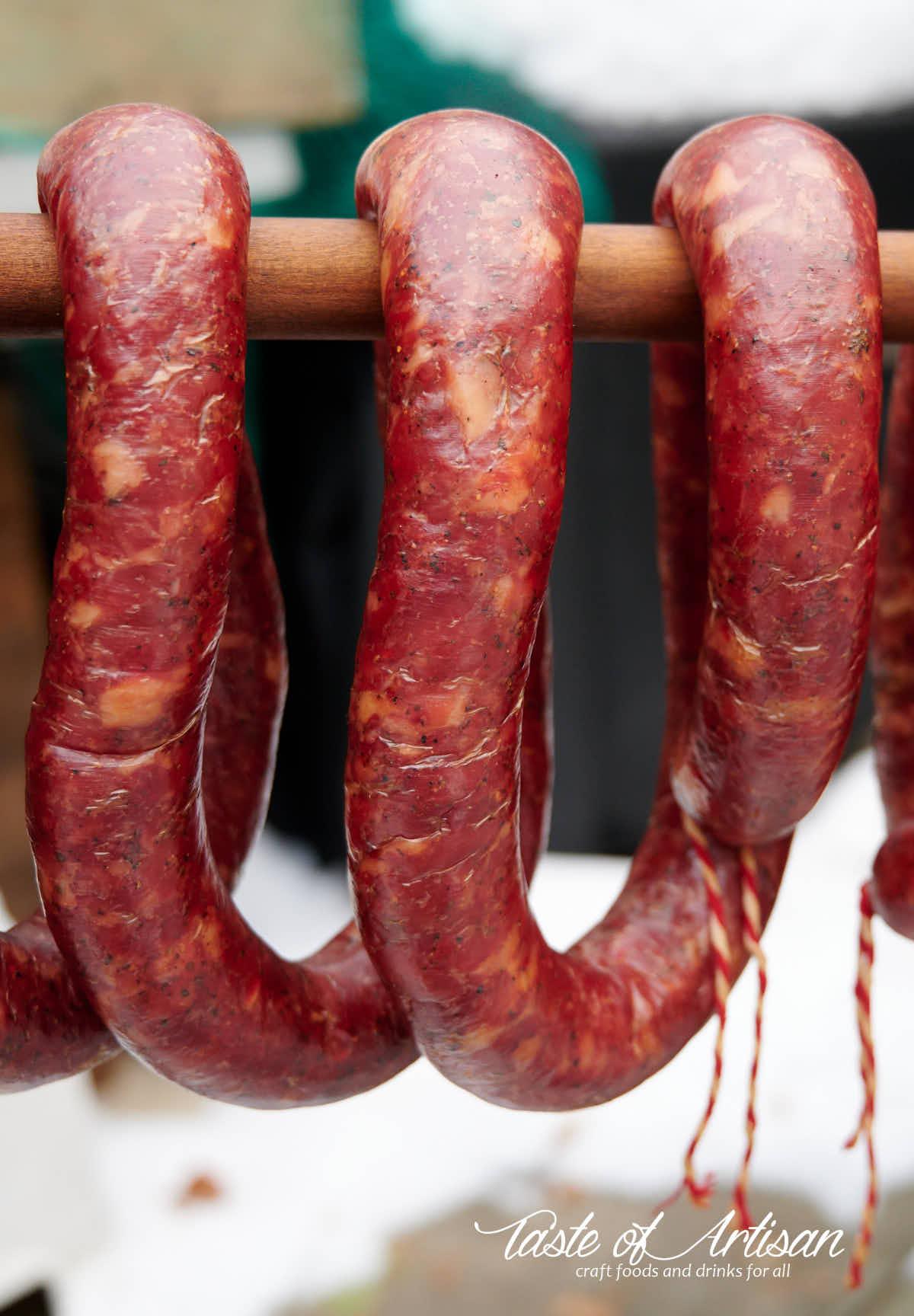 Smoked garlic sausage hanging on a stick.