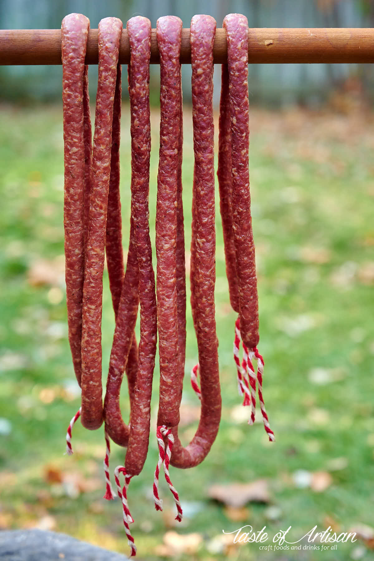Kabanos sausage hanging from a smoke stick.