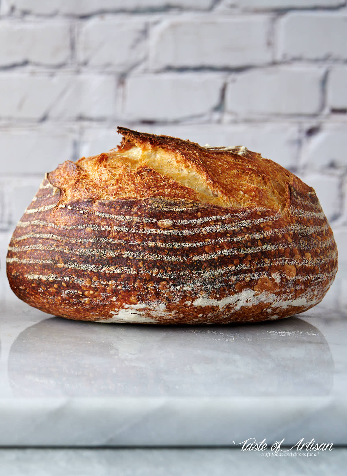 Whole no-knead sourdough bread on a marble slab.
